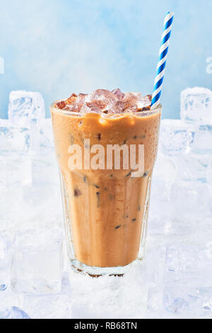 Summer drink ice coffee with cream in a tall glass with droplets and straw surrounded by ice cubes on snow over blue background. Selective focus, copy - Stock Photo