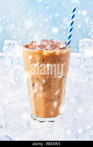 Winter drink ice coffee with cream in a tall glass with straw surrounded by ice cubes on snow over blue background with snow. Selective focus, copy sp