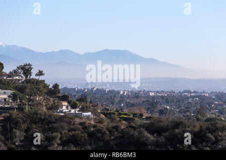 Smoggy morning cityscape view of hillside homes with Hollywood, Los Angeles and the San Gabriel Mountains in background. - Stock Photo