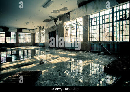 Interior of abandoned mental hospital with broken windows and water flood on floor - Stock Photo