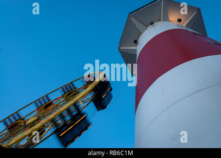 An amusement ride, spinning, beside a red and white tower against a rich blue evening sky - Stock Photo