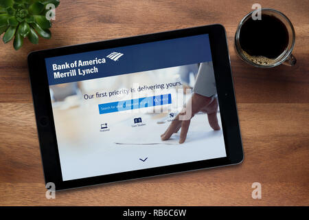 The website of Bank of America Merrill Lynch is seen on an iPad tablet resting on a wooden table (Editorial use only). - Stock Photo