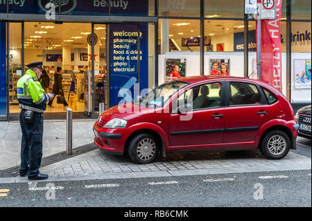 Traffic Warden/Parking Enforcer issues a ticket to an illegally parked car in Cork City, Ireland. - Stock Photo