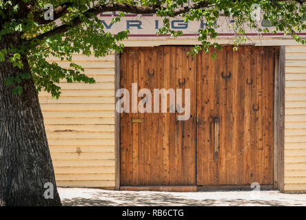 A large wooden double shed door with multiple hose shoes attached, on the side of the street in the sun with a tree in the foreground - Stock Photo