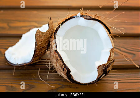 Pieces of open coconut on wooden table - Stock Photo