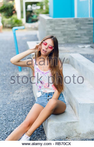 Cute stylish girl with blue background sits on porch and listens to music on earphones on smartphone. Girl wears short white tank, denim shorts, pink sunglasses and white sneakers. She is very slim. - Stock Photo