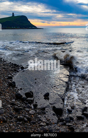 Landscape photograph in portrait orientation on Kimmeridge beach looking out upon washing ledge surrounded by rough swash under moody skies. - Stock Photo
