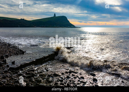 Landscape photograph on Kimmeridge beach looking out upon washing ledge surrounded by rough swash under moody skies. - Stock Photo