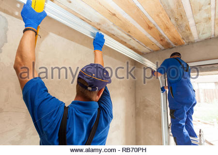 Garage doors installation. Workers installing  Post Rail and Spring Installation / Assembly. - Stock Photo