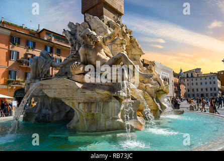 Rome, Italy - September 30 2018: Tourists visit the Fountain of the Four Rivers by Bernini in the Piazza Navona in Rome Italy as the sun goes down. - Stock Photo