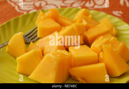 Delicious Healthy sweet papaya slices on a green plate with a fork - Stock Photo