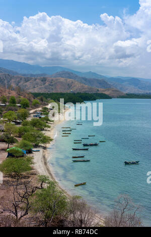 Fishing boats and a small village on the north coast of Timor Leste at the end of the dry season. - Stock Photo