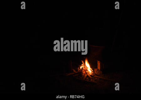 A bright camp fire with yellow and orange flames on a black dark background - Stock Photo