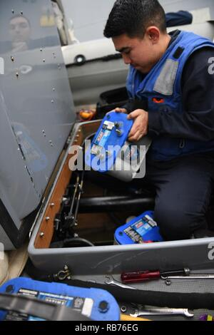 MEDITERRANEAN SEA (Dec. 11, 2016) - Seaman Jose Rodriguez, from Tampa, Florida, changes out a battery of a rigid-hull inflatable boat aboard USS Donald Cook (DDG 75), Dec. 11, 2016.  Donald Cook, an Arleigh-Burke class guided-missile destroyer, forward-deployed to Rota, Spain, is conducting naval operations in the U.S. 6th Fleet area of operations in support of U.S. national security interests in Europe and Africa. - Stock Photo