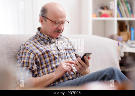 Mature hispanic man wearing eyeglasses checking messages on cell phone sitting on sofa in home living room - Stock Photo