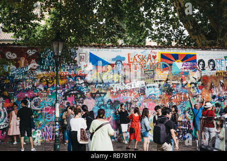 Prague, Czech Republic - August 23, 2018: People by John Lennon tribute wall in Prague. Started in 1980 by unknown artist, today the wall represents a - Stock Photo