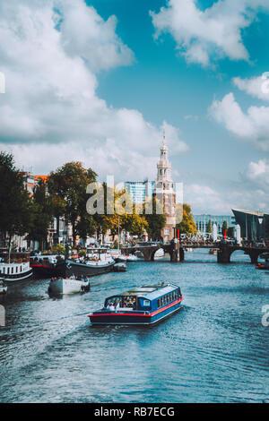 Boat on river Amstel in Amsterdam Netherlands landmark old european city landscape. Picturesque cloudscape - Stock Photo