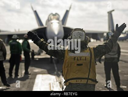 ATLANTIC OCEAN (Dec. 2, 2016) Petty Officer 3rd Class Jerome Gordon, from Tampa, Florida, directs an F/A-18E Super Hornet, assigned to the Flying Eagles of Strike Fighter Squadron (VFA 122), onto a catapult during flight operations aboard the aircraft carrier USS George Washington (CVN 73). George Washington, homeported in Norfolk, is underway conducting carrier qualifications in the Atlantic Ocean. - Stock Photo