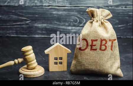 A bag of money with the word Debt and the family standing near the house and gavel. The concept of debt for housing. Mortgage. Real estate, loans mark - Stock Photo