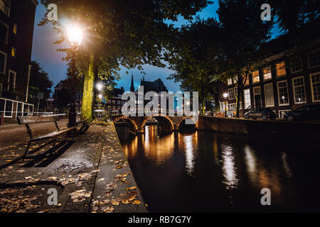 Tranquil scene of Amsterdam, autumn cityscape of beautiful bridge over canal. the Netherlands. Long exposure - Stock Photo