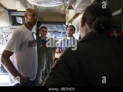 PEARL HARBOR (Dec. 5, 2016) Princeton University's men's basketball team Assistant Coach Kerry Kittles (left) from New Orleans, Louisiana, and player Devin Cannady (right), from Mishawaka, Indiana, talk to Sailors assigned to U.S. Navy Patrol Squadron Nine (VP-9) as they toured a P-3C Orion long-range anti-submarine warfare aircraft during a multi-service static display of airpower at Hickam Field on Joint Base Pearl Harbor-Hickam. The basketball team is in Hawaii to play in the FOX Sports Pearl Harbor Invitational held Dec. 6 - 7 at Bloch Arena on Pearl Harbor.  Dec. 7, 2016, marks the 75th a - Stock Photo
