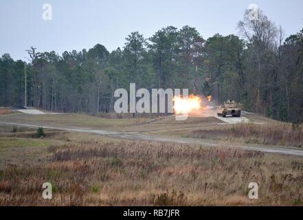 A M1A2 Abrams Main Battle Tank from 2nd Battalion, 7th Infantry Regiment engages a target with a 120mm main gun during their Gunnery Table VI engagements at Fort Stewart, Georgia Dec. 5. Tank crews from throughout 1st Armored Brigade Combat Team, 3rd Infantry Division are competing for bragging rights as tank crews look to qualify and prepare for future collective training. - Stock Photo
