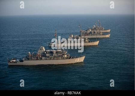 ARABIAN GULF (Dec. 6, 2016) The Avenger class mine countermeasure (MCM) ships USS Dextrous (MCM 13), USS Gladiator (MCM 11), USS Devastator (MCM 6), and USS Sentry (MCM 3), part of Commander, Task Force (CTF) 52, sail in formation as part of a photo exercise in the Arabian Gulf, Dec. 6, 2016. The combined MCM force enhances mine-hunting capabilities in searching, identifying and neutralizing mines threatening the freedom of navigation and the free flow of commerce. - Stock Photo