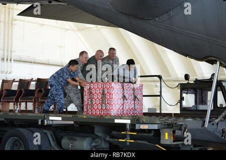 Leaders move a box of donated goods into the back of a C-130 Hercules during the 65th Operation Christmas Drop 'Push Ceremony' at Andersen Air Force Base, Guam, Dec. 6, 2016. Left to rIght: Rear Admiral Bette Bolivar, commander, Joint Region Marianas, Brig. Gen. Douglas Cox, 367th Wing commander, Andersen Air Force Base, Guam, Col. Kenneth Moss, 374th AIrlift Wing commander, Yokota Air Base, Japan, Col. Scott Zippwald, 515th Air Mobility Operations WIng commander, Joint Base Pearl Harbor Hickam, HI and Mr. Manny Hechanova, Associate Director of Telecommunications and Distance Education Operati - Stock Photo