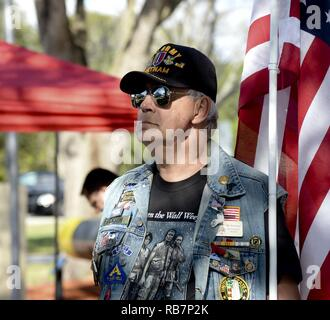 "Army veteran Bill Erickson, holds a flag during the Pearl Harbor Remembrance Day ceremony at Veterans Memorial Park in Tampa, Fla., Dec. 7, 2016. Service members, veterans, retirees and civilians gathered to commemorate the 75th anniversary with a ceremony themed ""We Remember the Fallen."" - Stock Photo"
