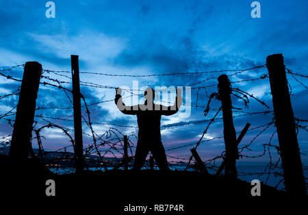 silhouette of man looking through barbed wire/ razor wire fence at night. Brexit, immigration, asylum... concept - Stock Photo