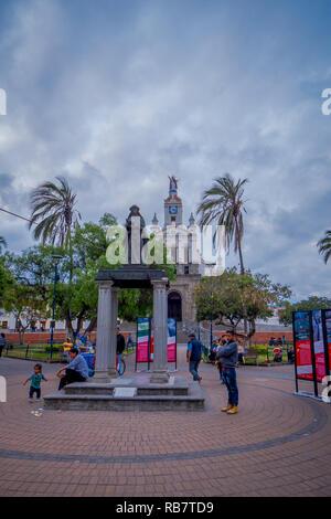 COTACACHI, ECUADOR, NOVEMBER 06, 2018: People walking in front of Calderon Park, Cotacachi, Ecuador - Stock Photo