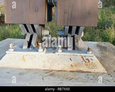 Steel tie joint with swing  beam and anchored into concrete. Modern foot bridge base. - Stock Photo