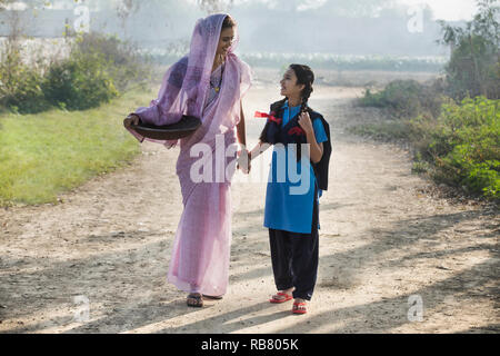 Female farmer or rural woman walking on village street along with her school going daughter carrying an iron gold pan. - Stock Photo