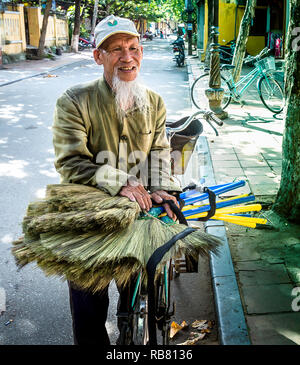 Older grey bearded man selling brooms from his bicycle on the streets of Vietnam. - Stock Photo