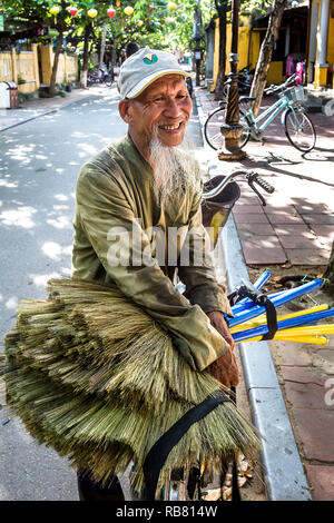 Old Vietnamese man selling brooms on the street. - Stock Photo