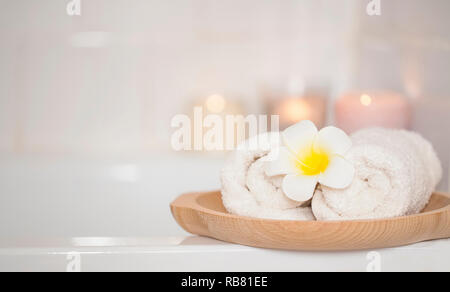 Spa still life with towels and frangipani flower, home spa setting still life - Stock Photo
