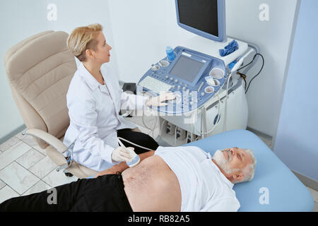 Top view of doctor observing patient with modern medical equipment to exam some problems. senior man laying on bed and consulting with professional doctor. Woman looking at screen and working. - Stock Photo