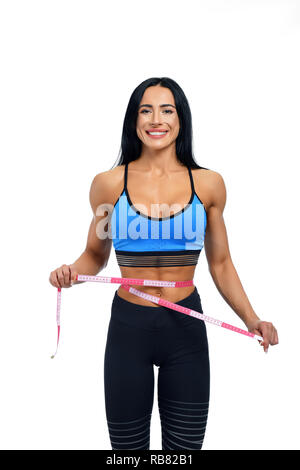 Happy woman with black hair regularly going to gym. Young starting athlet ready for body measuring before final. Strong personal trainer with big muscles waiting for clients with unique programme. - Stock Photo