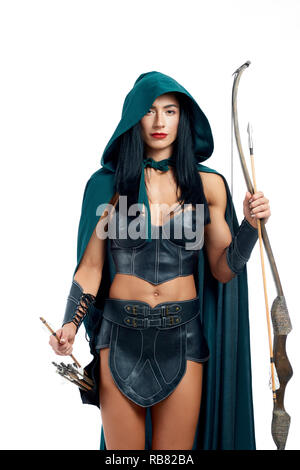 Beautiful and young girl making cosplay of fantasy creature. Gorgeous archery in emerald mantle with hood and leather armor posing at camera. Elegant woman holding bow and arrow and ready for fight. Stock Photo