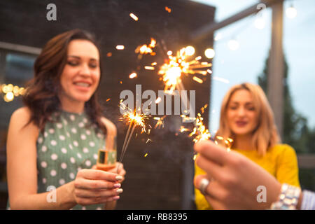Group of partying girls with flutes with sparkling wine and bengal fire having fun on the party - Stock Photo