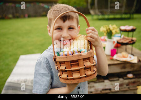 Young boy standing outdoors holding a basket full of chocolate easter eggs that he found on the easter egg hunt. - Stock Photo