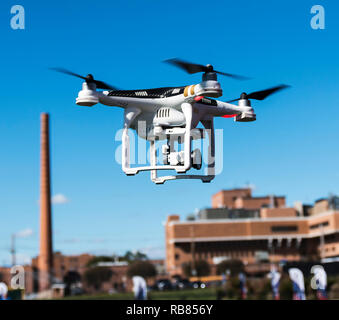 A drone with a camera is taking off from a field with a local hospital in the background and blue sky's above. - Stock Photo
