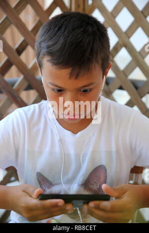 11-year-old boy using a cell phone in Salento, Italy. - Stock Photo