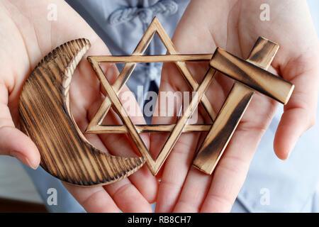 Symboles interreligieux. Christianity, Islam, Judaism 3 monotheistic religions. Jewish Star, Cross and Crescent : Interreligious symbols in hands. - Stock Photo