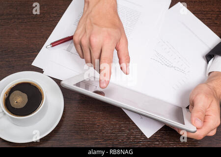 Successful businessman uses the Internet on his tablet PC, in the workplace are documents with schedules and a Cup of coffee. - Stock Photo