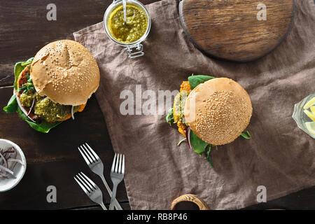 Vegetarian pumpkin burger with vegetarian pesto sauce on wooden table top view. Healthy vegetarian food concept - Stock Photo