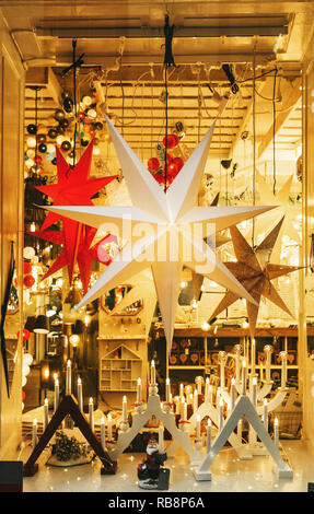 Christmas stars and candles decorations in window. Festive decor in the shop window .Stockholm, Sweden - Stock Photo