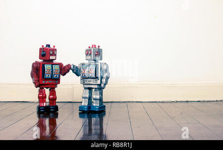 big red and silver robots holding hands with love on an old wooden floor copy space - Stock Photo