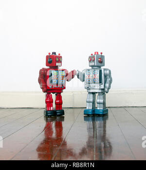 big red and silver robots holding hands with love on an old wooden floor - Stock Photo