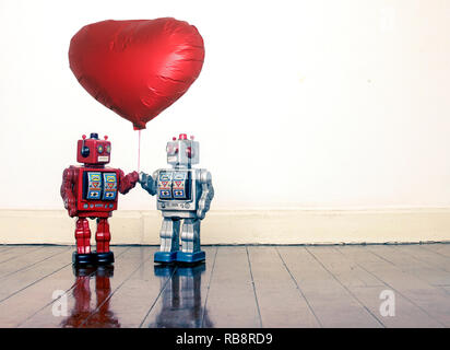 two vintage robots looking at each other both holding a big red balloon standing on an old wooden floor - Stock Photo